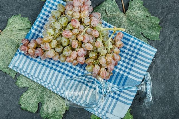 Un grappolo d'uva rossa e un bicchiere di vino sulla tovaglia blu con foglie. foto di alta qualità