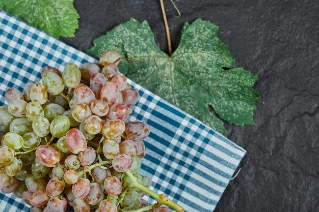 Un grappolo di uva rossa con foglie su sfondo scuro. foto di alta qualità