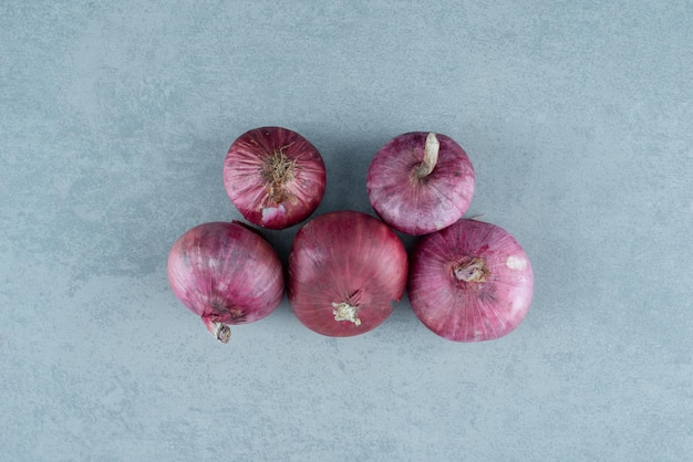 Bunch of red onions on marble.
