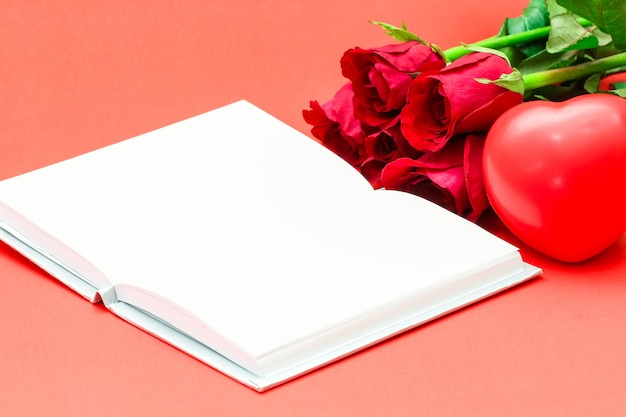 Bunch of red rose with sponge heart and white opened book on red surface