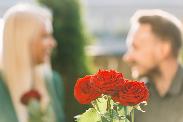 Bunch of red roses in front of couple looking at each other