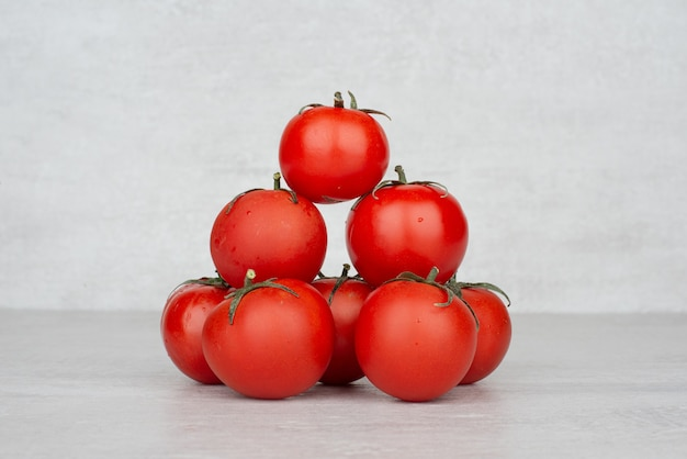 Bunch of red tomatoes on white table.