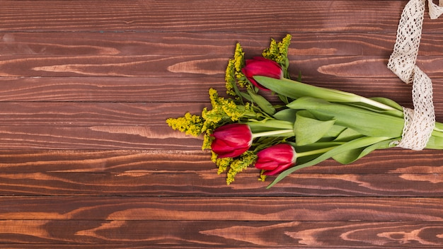 Bunch of red tulip flowers and goldenrod flowers tied up with lace against wooden background