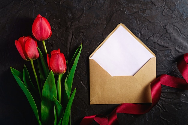 Bunch of red tulip flowers with envelope card and ribbon