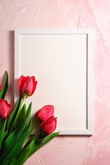 Bunch of red tulip flowers with picture frame template on textured pink surface, top view copy space