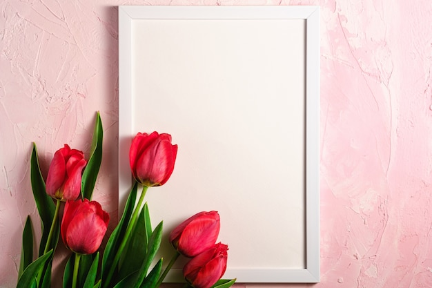 Bunch of red tulip flowers with picture frame template on textured pink wall, top view copy space