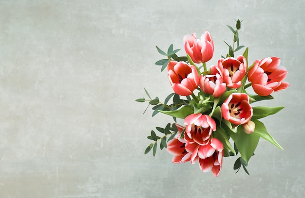 Bunch of red tulips and eucalyptus leaves on grey, top view, text space