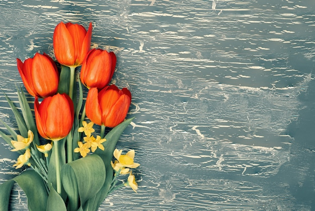 Bunch of red tulips and lily of the valley flowers on rustic background