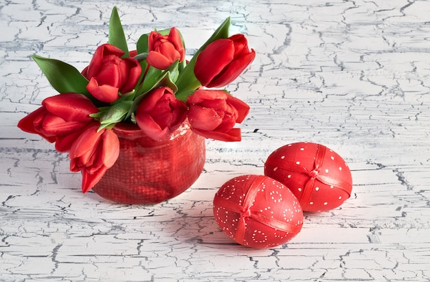 Bunch of red tulips and two red easter eggs on white rustic background