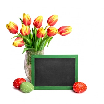 Bunch of red tulips with yellow tops, chalk board and colored easter eggs on white, text space