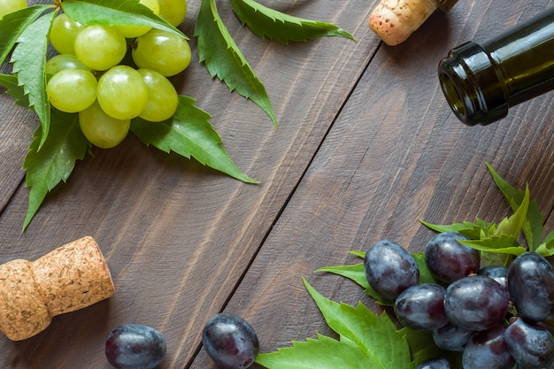 Bunch of red and white grapes, bottle of wine and cork on wooden table background