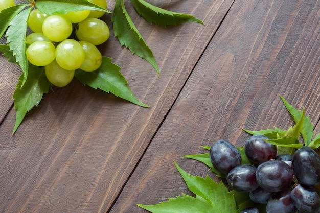 Bunch of red and white grapes on wooden table background