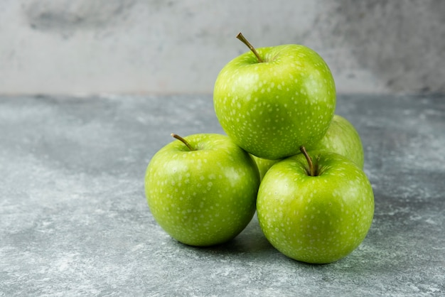 Bunch of ripe apples on marble.