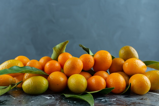 Bunch of ripe kumquats with green leaves on marble surface.
