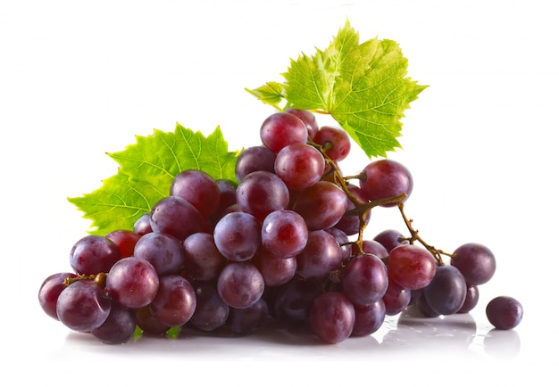 Bunch of ripe red grapes with leaves isolated on white