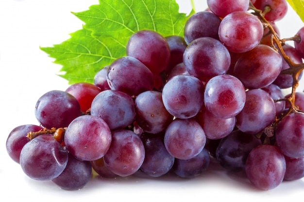 Bunch of ripe red grapes with leaves isolated
