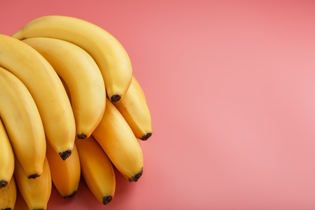 A bunch of ripe yellow bananas on a pink background. the view from the top. minimalistic concept. free space