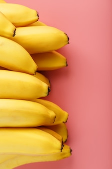 A bunch of ripe yellow bananas on a pink background.