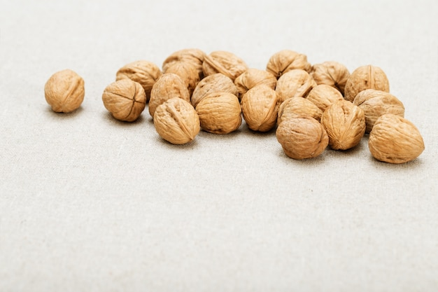 Bunch of round whole walnuts on a very light blurred fabric background.