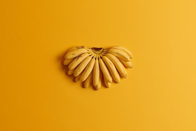 Il mazzo di piccole banane mature contiene nutrienti essenziali per la salute isolati su sfondo giallo. concetto di frutta estiva. vista piana, vista dall'alto. fonte di vitamine naturali. dieta e cibo sano