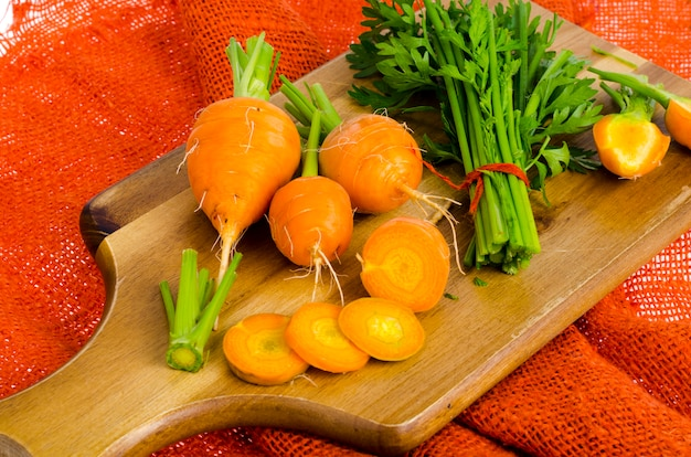 Bunch of small, round carrots (parisian heirloom carrots) on wooden background.