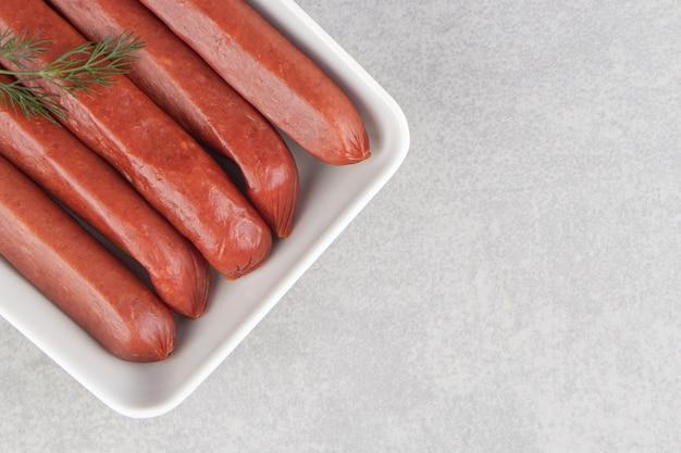 Mazzo di salsicce affumicate sul piatto bianco.