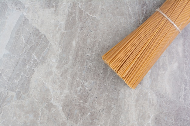 Un mazzo di spaghetti isolato sul marmo.