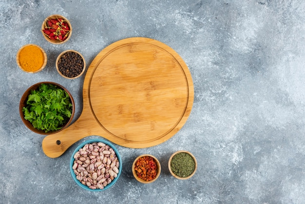 Bunch of spices and bowl of beans on marble background.