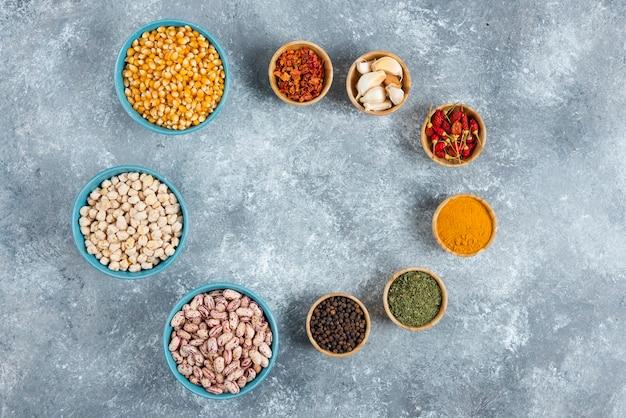 Mazzo di spezie e ciotole di fagioli, semi su sfondo marmo.