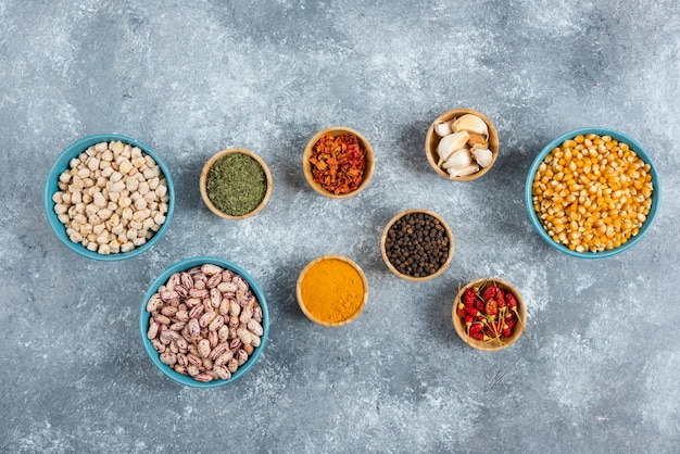 Bunch of spices and bowls of beans, corns on marble background.