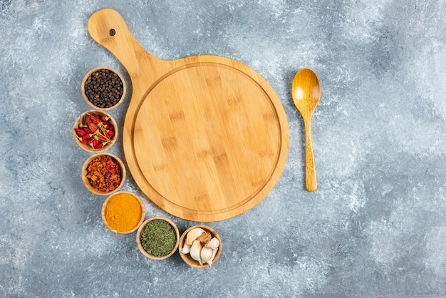 Bunch of spices with wooden board on marble background.