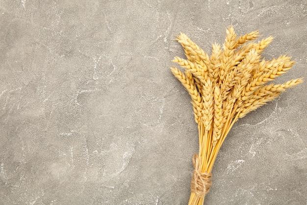 Куча колоски пшеницы на сером фоне бетона