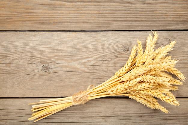 Куча колоски пшеницы на сером фоне деревянных