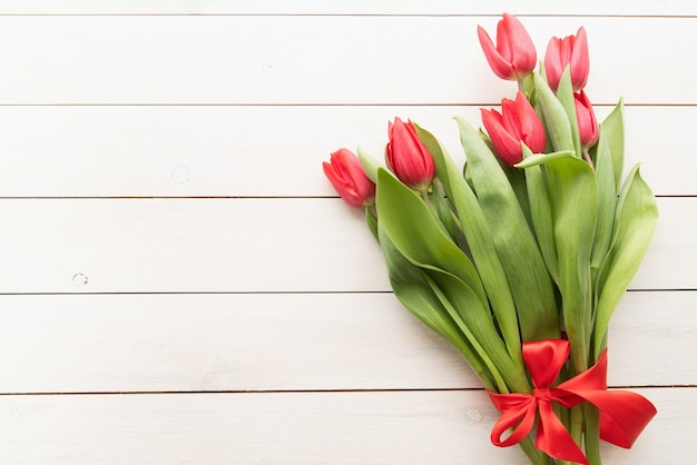 Bunch of spring tulips over white wooden background, top view flat lay