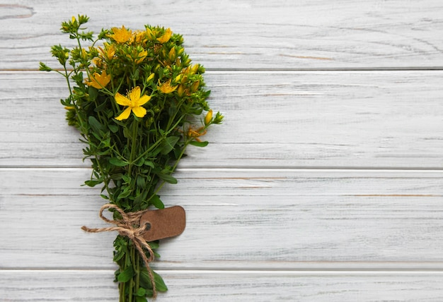 Bunch of st. john's wort with a tag on a white wooden surface