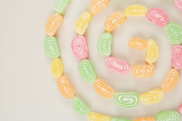 Bunch of sweet jelly candies on beige surface