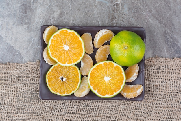 Bunch of tangerine and segments on black plate.