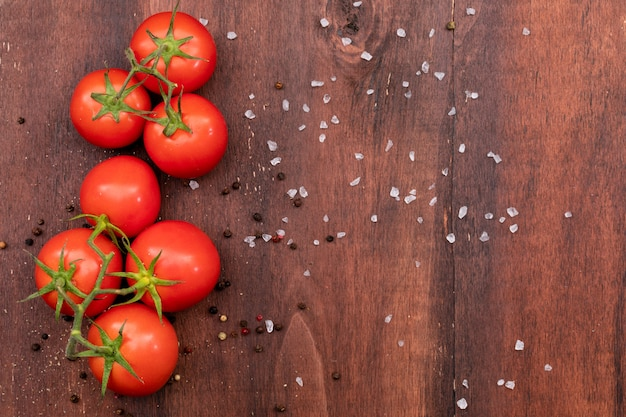 Bunch of tomato on wooden texture with scattered salt