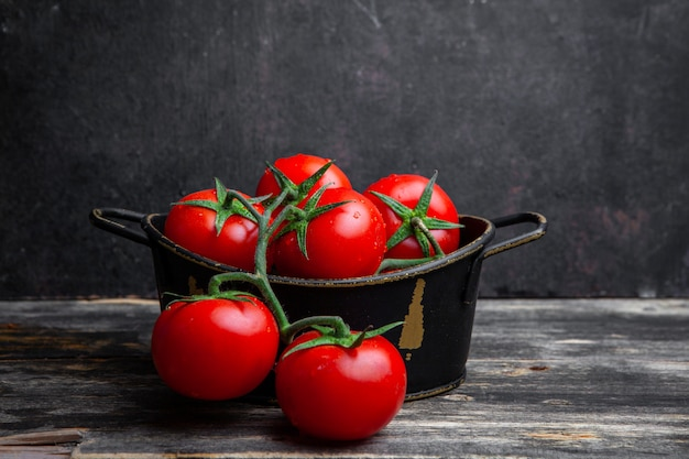 A bunch of tomatoes in a pot on a old wooden and black background. side view.