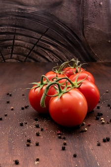 Bunch of tomatoes surrounded with pepper powder on the table side view
