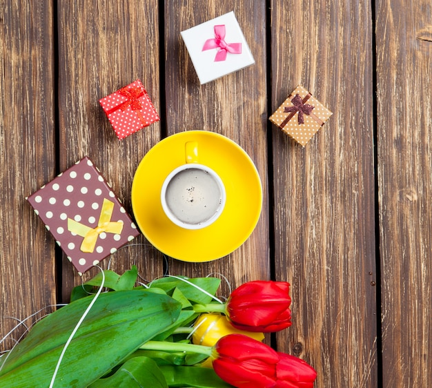 Bunch of tulips, cute gifts and cup of coffee on the wonderful brown wooden background