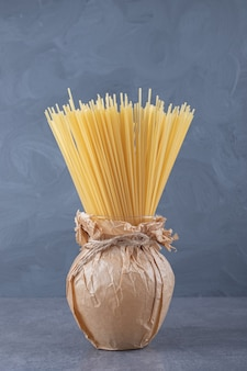 Bunch of uncooked dry spaghetti in vase.