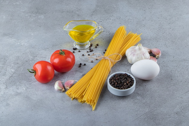Bunch of uncooked spaghetti in rope with fresh red tomatoes and garlic.