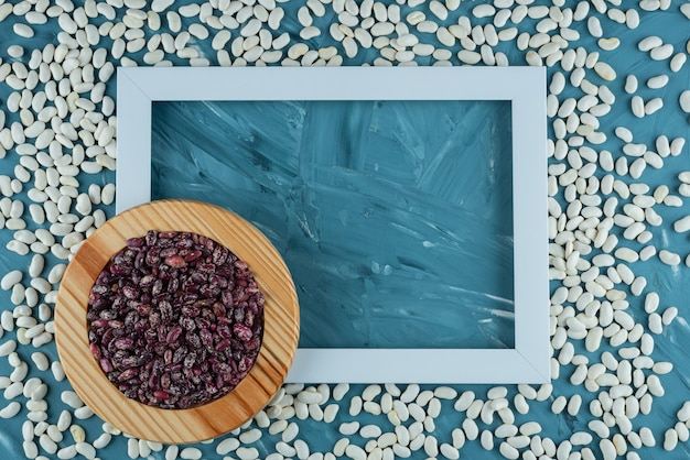 Bunch of various raw beans scattered on blue background with frame.