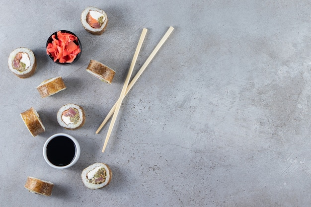 Bunch of various sushi rolls and soy sauce on stone background.