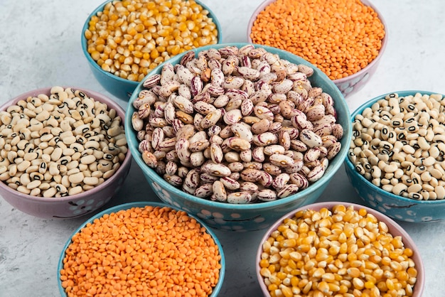 Bunch of various uncooked beans, corns and red lentils on marble surface.