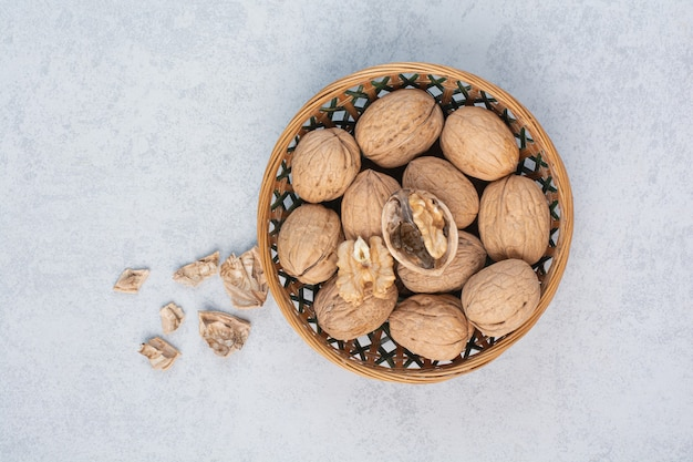 Bunch of walnuts and kernels in ceramic bowl