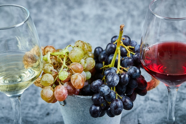 Bunch of white and black grapes and two glasses of white and red wine on blue.