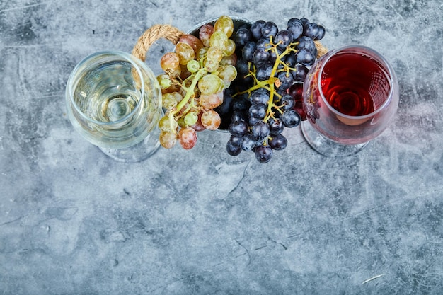 Bunch of white and black grapes and two glasses of white and red wone on blue.