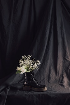 Bunch of white blooms in dark leather boot